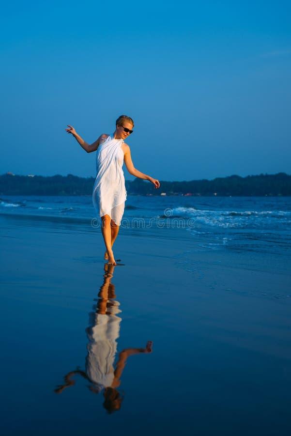 Presentación rubia hermosa y atractiva feliz joven contra el mar azul en el vestido y las gafas de sol blancos Muchacha elegante  imagen de archivo
