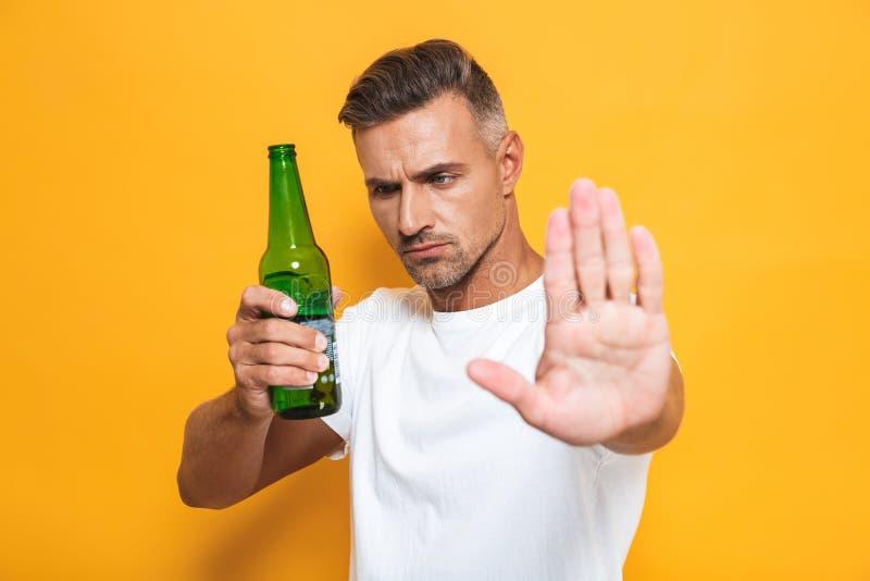 Presentación seria del hombre aislada sobre la botella amarilla de la tenencia del gesto de la parada de la demostración del fond imagen de archivo