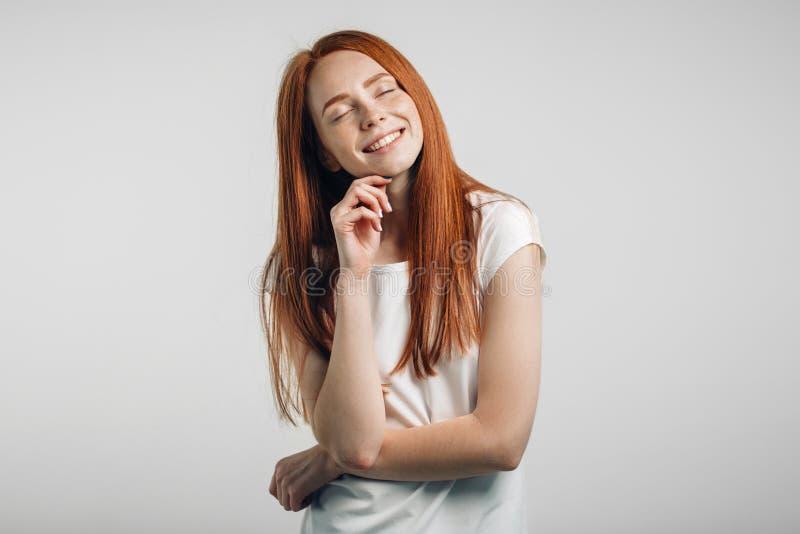 Presentación sonriente de la muchacha hermosa del jengibre con los ojos cerrados imagen de archivo