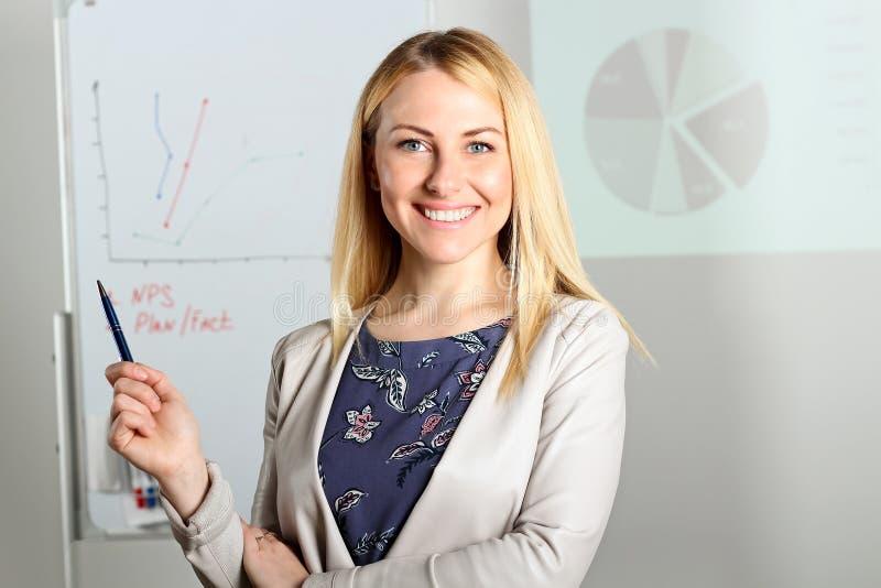 Presentación sonriente de la mujer de negocios Presentación en un fondo imagen de archivo