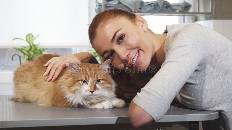 Presentación sonriente de la mujer magnífica con su gato en la oficina del veterinario foto de archivo libre de regalías