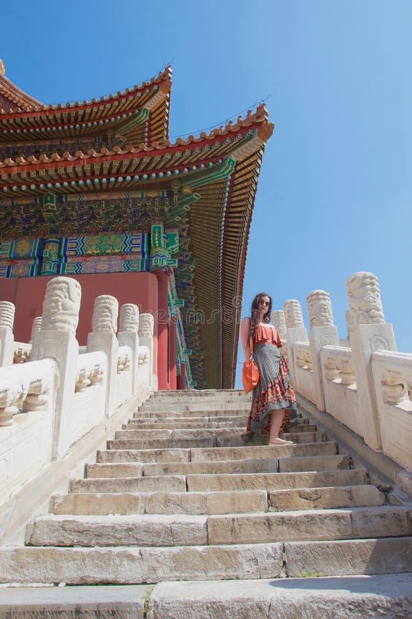 Presentación turística de la señora morena caucásica en pasos del edificio chino tradicional imagen de archivo libre de regalías