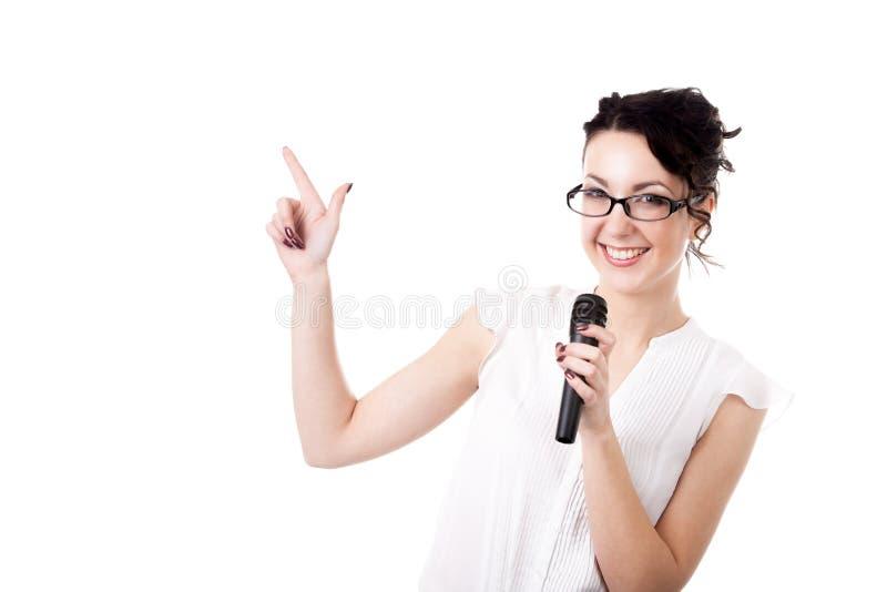 Presentador joven de la mujer de la oficina con el micrófono en el fondo blanco imagenes de archivo