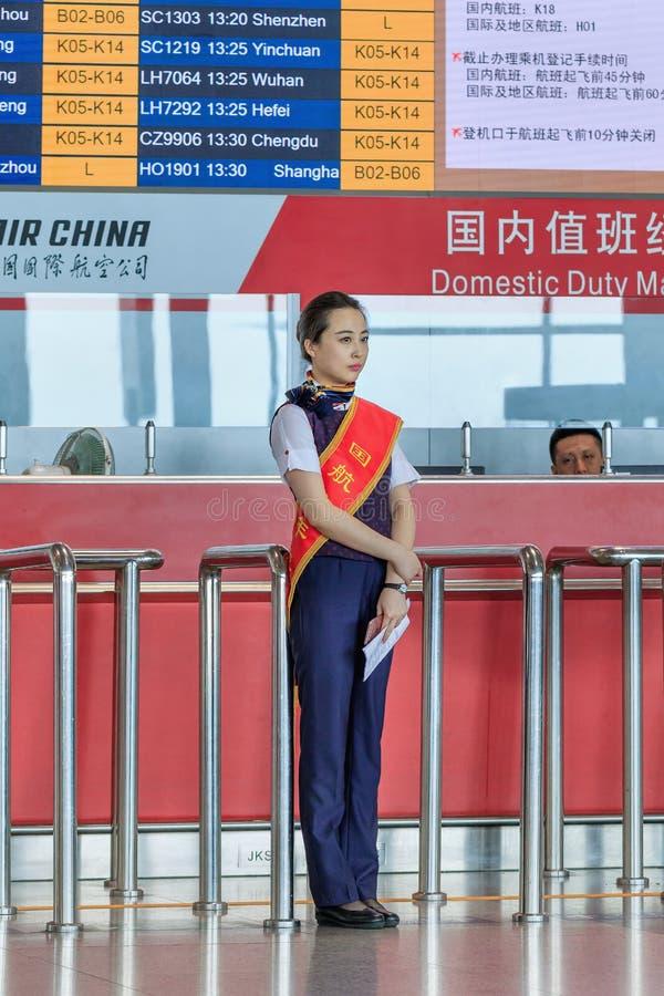 Presentadora encantadora delante del escritorio en el aeropuerto internacional capital de Pekín imágenes de archivo libres de regalías
