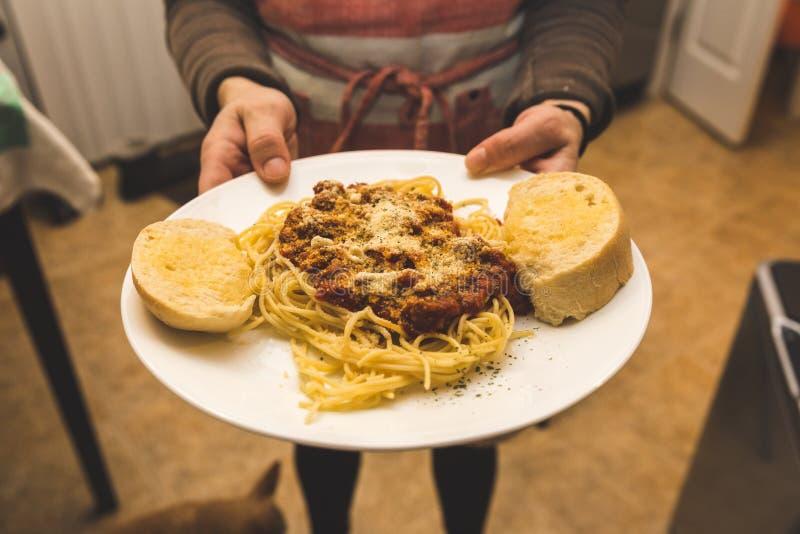 Presentando un piatto in pieno degli spaghetti e del pane fotografia stock libera da diritti