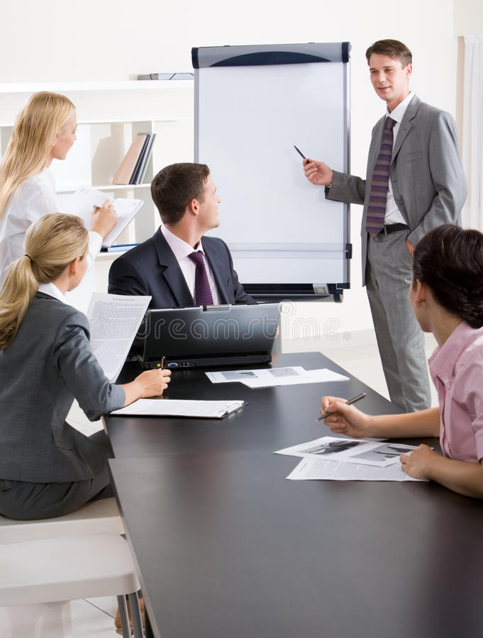 Presentation. Image of confident businessman doing a presentation while their partners listening to it royalty free stock images