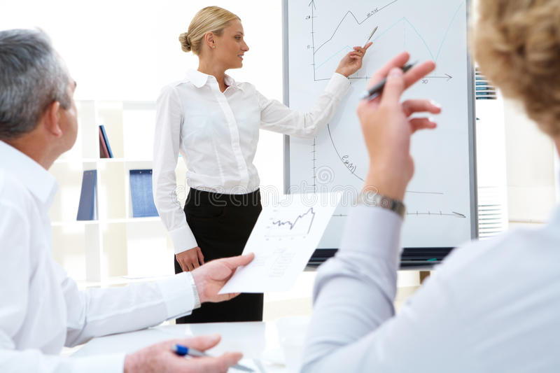 Presentation. Photo of successful manager standing by whiteboard while her colleagues listening to her stock photography