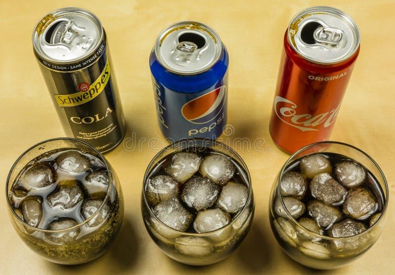 Presentation av cola-stil en kolsyrad dryck från olika producenter: Pepsi, coca - cola och Schweppes, som hälldes in i gl arkivbilder