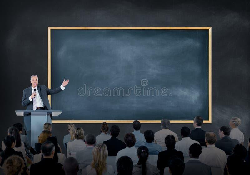 Presentation av en högtalare till en stor grupp av affärsfolk royaltyfria foton