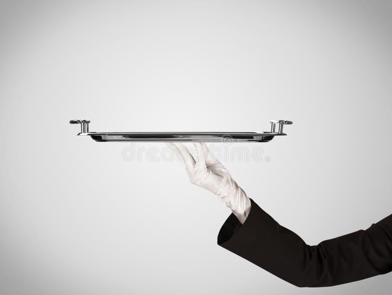 Presentation på plattan vid den stilfulla handen royaltyfri foto