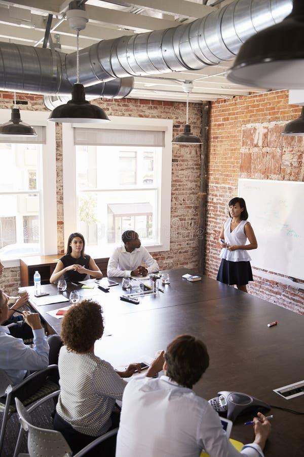Presentazione di At Whiteboard Giving della donna di affari in sala del consiglio immagini stock libere da diritti