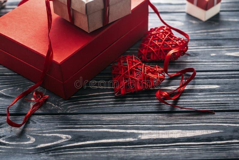 Presente alla moda di rosso e due nastri del cuore su di legno rustico nero fotografia stock