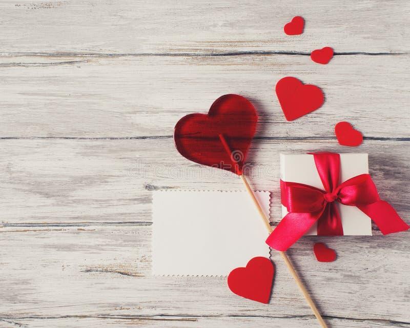 Presente atual com nota vermelha da placa do pirulito dos doces dos corações da fita sobre imagens de stock