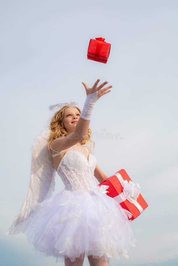 Presente atual do anjo Menina do anjo do querubim adolescente com o presente para o seu Crian?a com car?ter ang?lico Dia feliz do foto de stock royalty free
