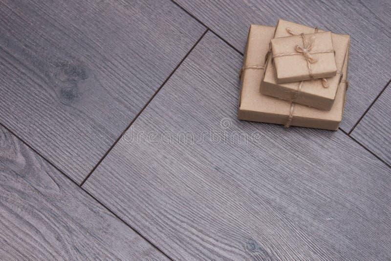Presente avvolto in carta del mestiere con la corda del sacco su fondo di legno Più piccolo o più grande Spazio vuoto immagine stock libera da diritti
