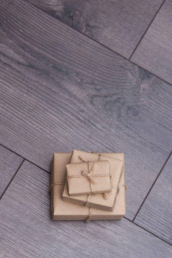 Presente avvolto in carta del mestiere con la corda del sacco su fondo di legno Spazio vuoto fotografie stock