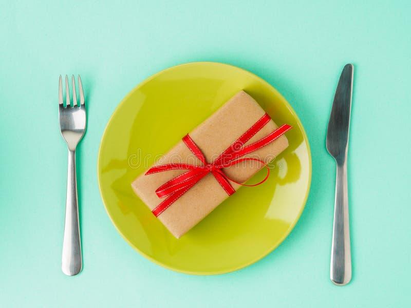 Presente, bloco do papel marrom de Kraft com a fita vermelha na placa amarela, foto de stock royalty free