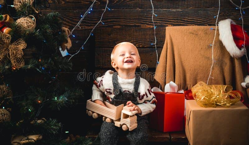 Presente bonito da abertura da criança pequena perto da árvore de Natal Feliz Natal e ano novo feliz O menino da criança que ri e imagem de stock royalty free