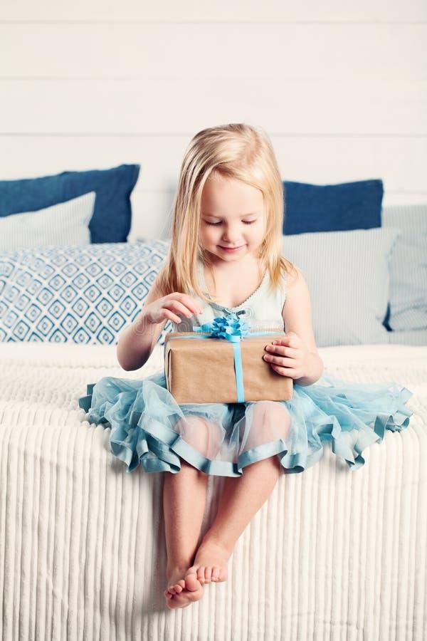 Presente bonito da abertura da menina da criança com fita azul fotografia de stock