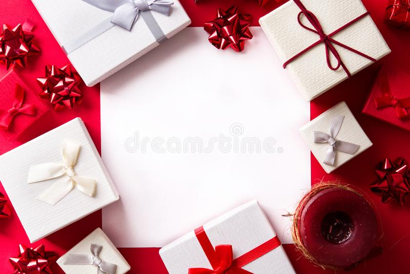 Presente branco e vermelho no fundo vermelho com o cartão de papel para o texto Conceito do Natal fotografia de stock