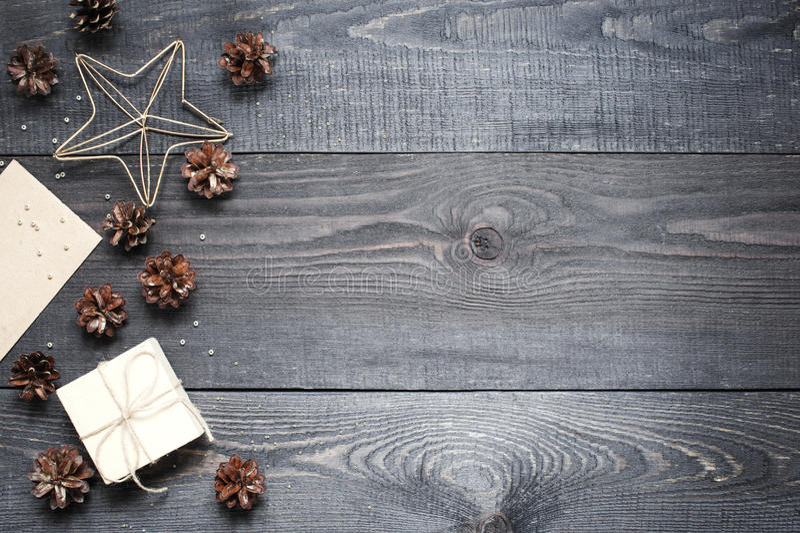 Presente, cartão, cones do pinho e cinnamonin na textura de madeira escura imagem de stock royalty free