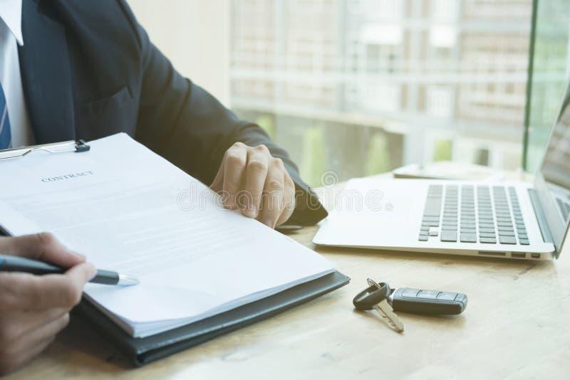 Presente contratto di firma di vendite dell'uomo d'affari con la chiave dell'automobile al custo immagine stock libera da diritti