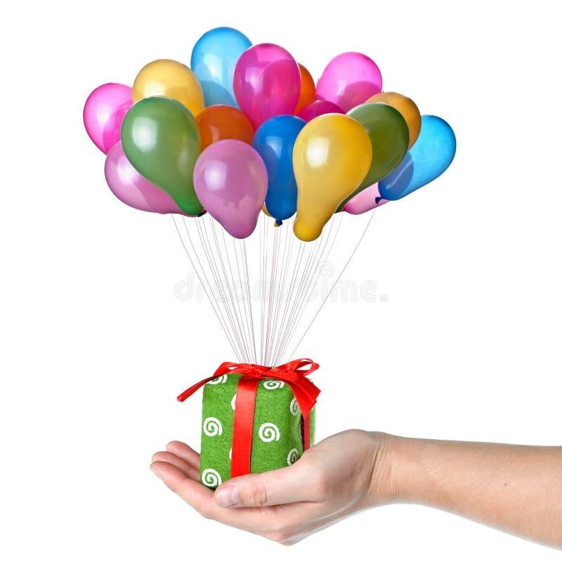 Presente da terra arrendada da mão com balões da cor fotos de stock