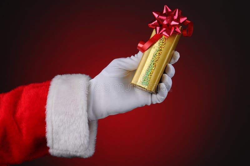 Presente da terra arrendada da mão de Papai Noel foto de stock royalty free