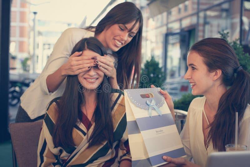 Presente de aniversário surpresa Jovens mulheres imagem de stock
