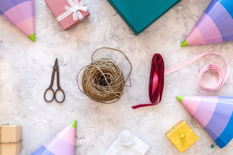 Presente de empacotamento Caixas de presente coloridas, sciccors, cabo fino, fita, chapéu do partido na opinião superior do fundo fotografia de stock
