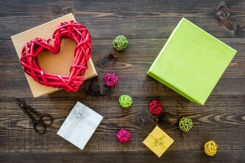 Presente de empacotamento Caixas de presente coloridas, sciccors, cabo fino na opinião superior do fundo de madeira escuro fotografia de stock