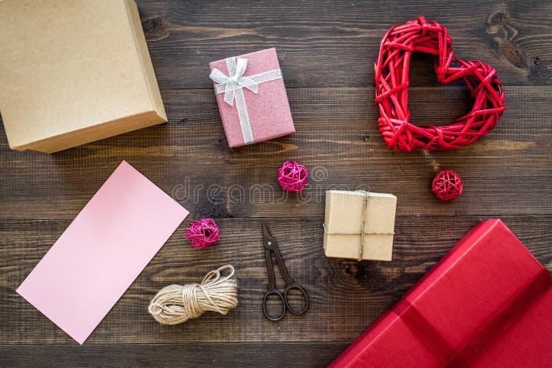 Presente de empacotamento Caixas de presente coloridas, sciccors, cabo fino na opinião superior do fundo de madeira escuro fotos de stock royalty free