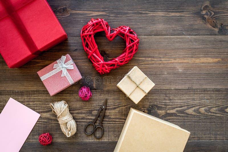 Presente de empacotamento Caixas de presente coloridas, sciccors, cabo fino no copyspace de madeira escuro da opinião superior do fotografia de stock
