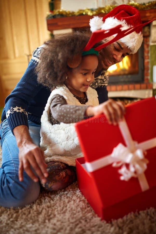 Presente de Natal aberto da menina afro pequena de seu paizinho fotografia de stock