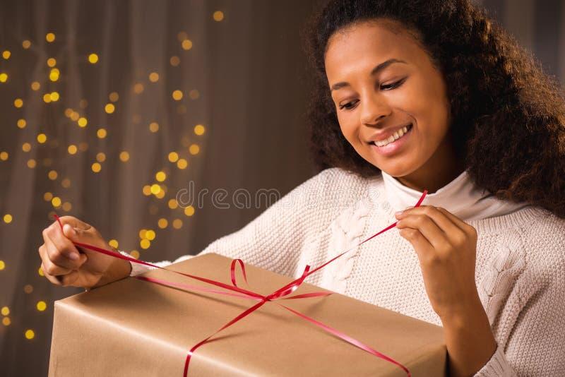Presente de Natal da abertura da jovem mulher imagem de stock