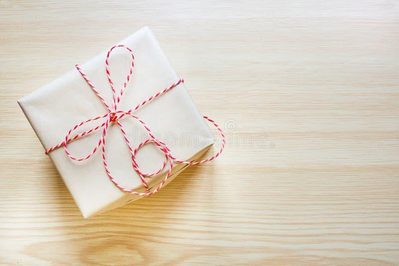 Presente de Natal envolvido no papel do ofício com a fita na placa de madeira Vista superior fotografia de stock royalty free