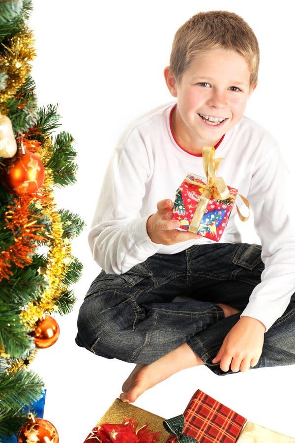 Presente de Natal novo da terra arrendada do menino foto de stock