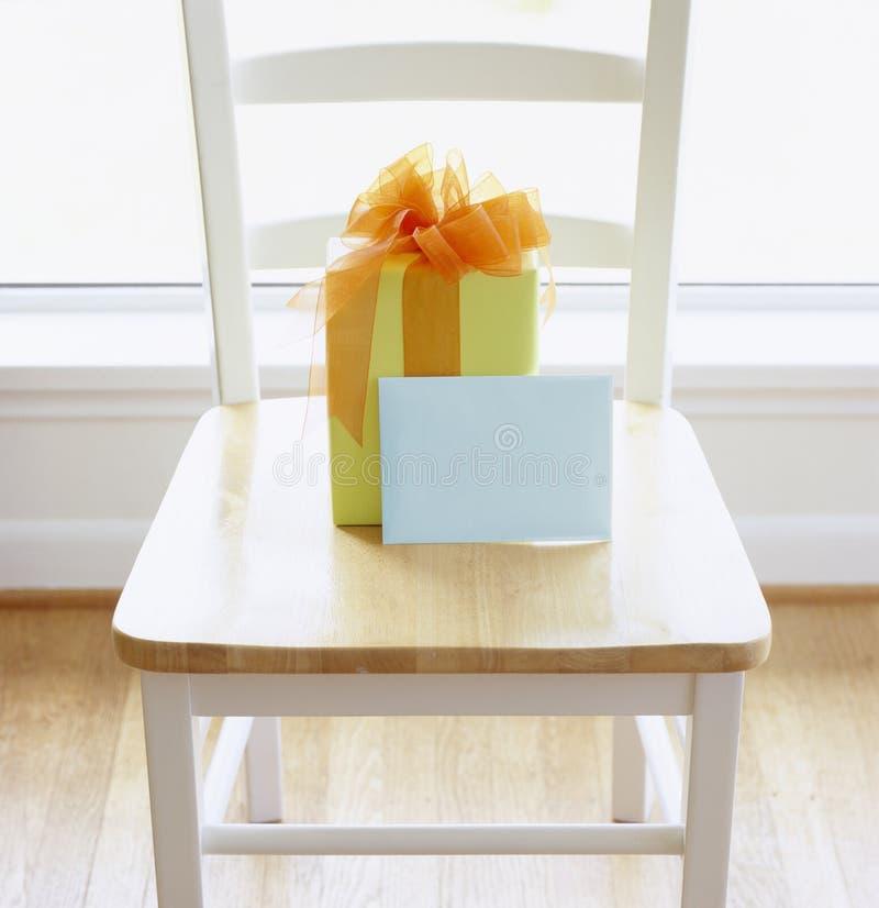 Presente del regalo con carta da imballaggio variopinta e l'arco e cartolina d'auguri con la busta in bianco sulla sedia di legno immagini stock