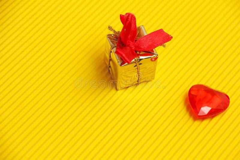 Presente dell'oro o contenitore di regalo con l'arco e nastri rossi e cuore plasstic rosso su fondo giallo con il modello diagona fotografie stock