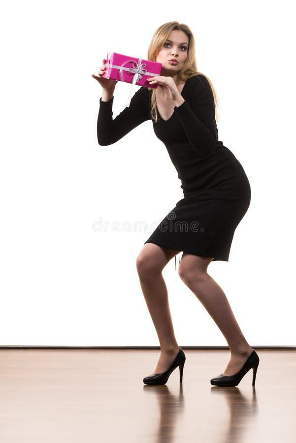 Presente della tenuta della ragazza che scuote il contenitore di regalo rosa fotografia stock libera da diritti