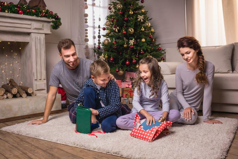 Presente di apertura della famiglia sulla notte di Natale fotografia stock