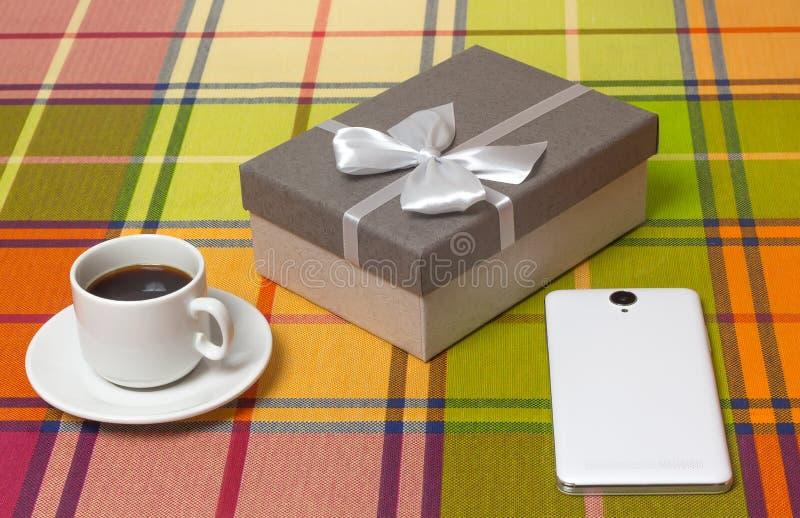 Presente do café no smartphone da caixa na tabela imagens de stock
