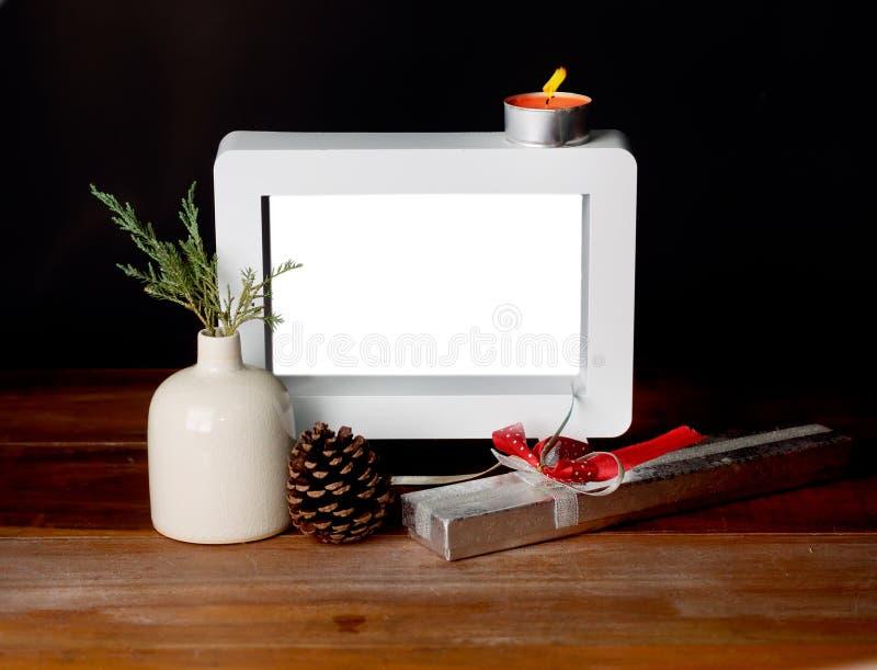 Presente do Natal com moldura para retrato vazia na tabela de madeira foto de stock