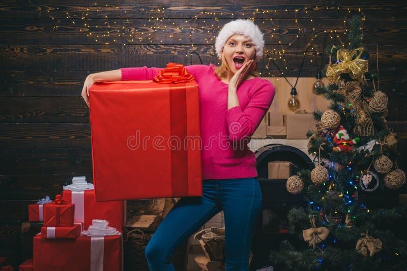 Presente do Natal Feliz Natal e ano novo feliz Mulher do inverno que veste o chapéu vermelho de Papai Noel Presentes do ano novo fotografia de stock