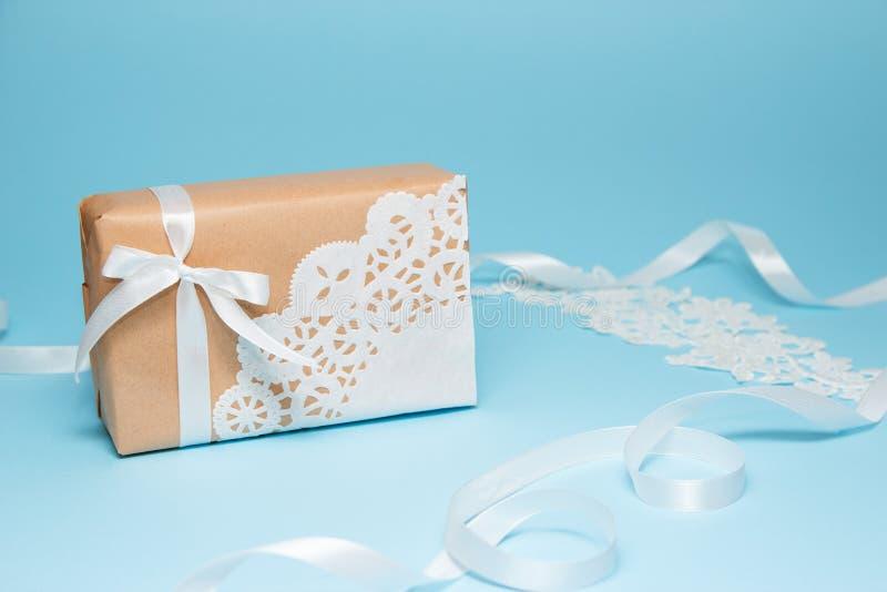 Presente do papel de embalagem decorado com um guardanapo do laço em um fundo de papel azul Cartão do feriado fotografia de stock royalty free