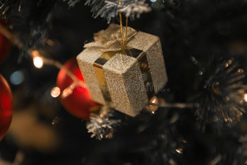 Presente dourado do Natal em uma árvore bonita de Chrismas cercada imagem de stock
