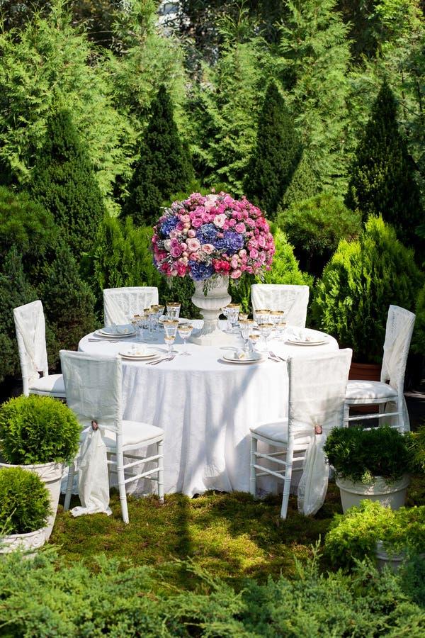 Presente el ajuste en una recepción nupcial de lujo en el jardín imagen de archivo libre de regalías