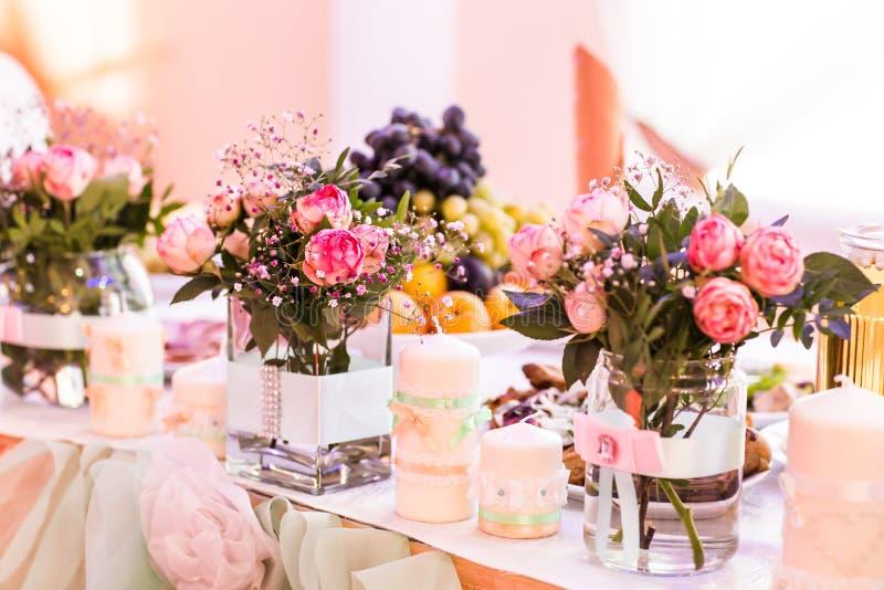 Presente el ajuste para un evento de la boda o de la cena, con las flores en el florero de vidrio imágenes de archivo libres de regalías