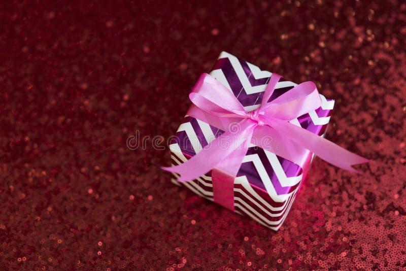 Presente/presente em um pano vermelho da lantejoula fotografia de stock royalty free