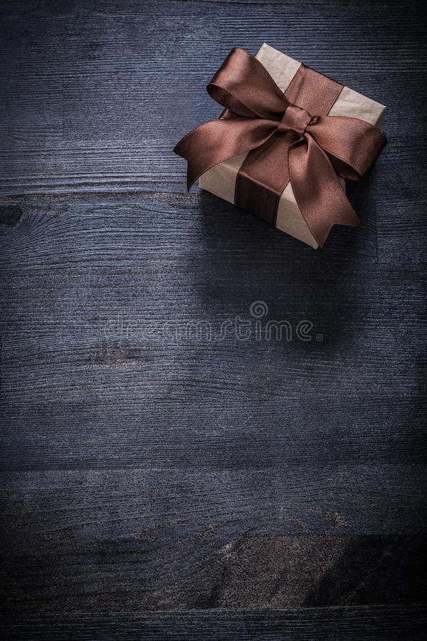 Presente encajonado con el arco atado en el copyspace de madera del tablero del vintage fotografía de archivo libre de regalías